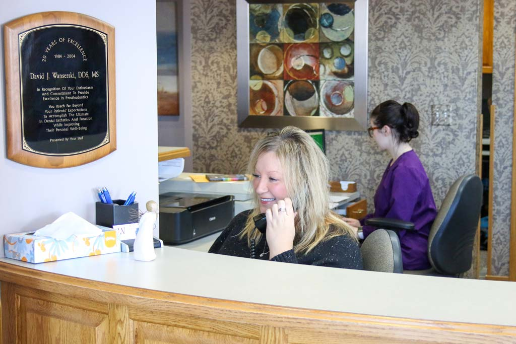 A smiling receptionist attending a call at the recption desk with a smiling hygienist sitting behind her at Wanserski Dental Center for Complex Dentistry